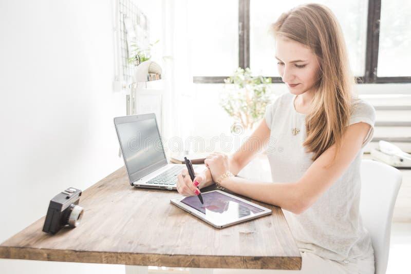 Η νέα εργασία επιχειρησιακών γυναικών στο σπίτι και επισύρει την προσοχή στην ταμπλέτα Δημιουργικός Σκανδιναβικός χώρος εργασίας  στοκ φωτογραφία