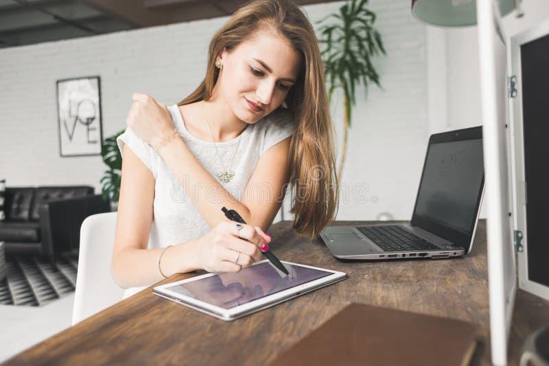 Η νέα εργασία επιχειρησιακών γυναικών στο σπίτι και επισύρει την προσοχή στην ταμπλέτα Δημιουργικός Σκανδιναβικός χώρος εργασίας  στοκ φωτογραφίες