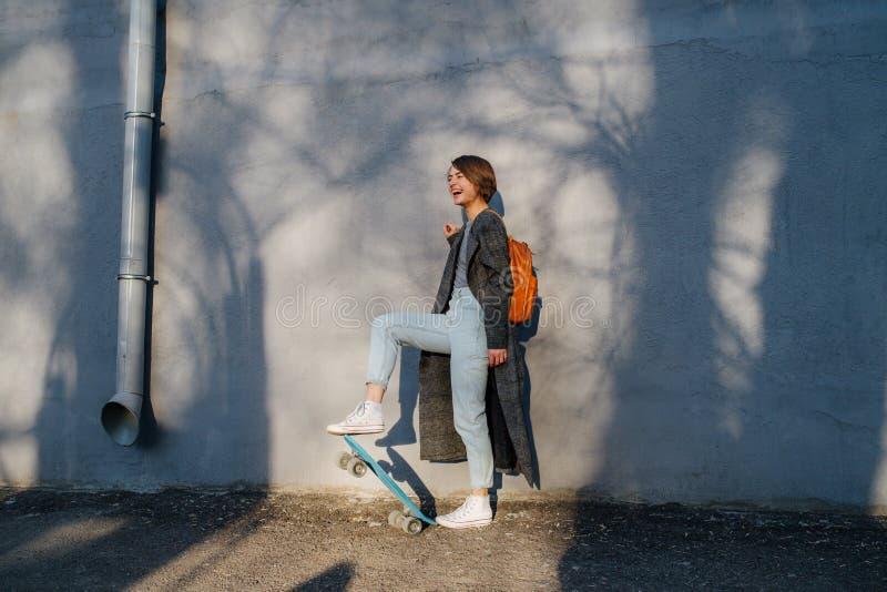 Η νέα ευτυχής με κοντά μαλλιά γυναίκα brunette παίρνει έναν περίπατο με το σαλάχι σε μια πόλη στοκ εικόνες
