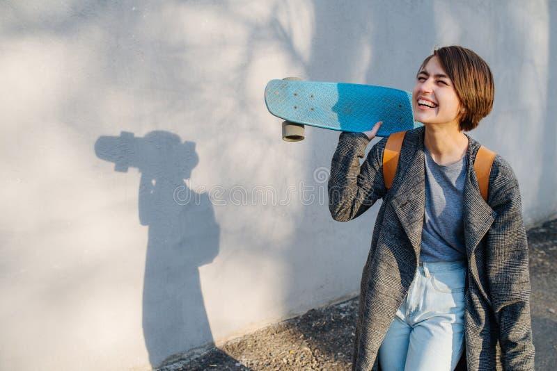 Η νέα ευτυχής με κοντά μαλλιά γυναίκα brunette με το σαλάχι παραδίδει μέσα το μέτωπο ενός τοίχου στοκ φωτογραφία με δικαίωμα ελεύθερης χρήσης