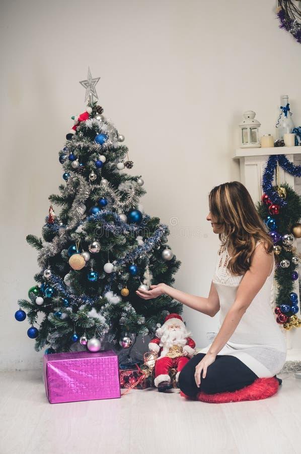 Η νέα ευτυχής όμορφη γυναίκα με τα κιβώτια δώρων κάθεται κοντά στο διακοσμημένο χριστουγεννιάτικο δέντρο στο δωμάτιο του σπιτιού  στοκ εικόνα με δικαίωμα ελεύθερης χρήσης