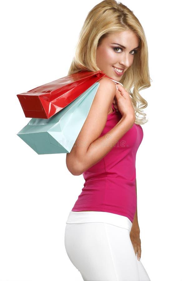 Η νέα ευτυχής όμορφη ξανθή γυναίκα πηγαίνει στις αγορές στοκ εικόνες