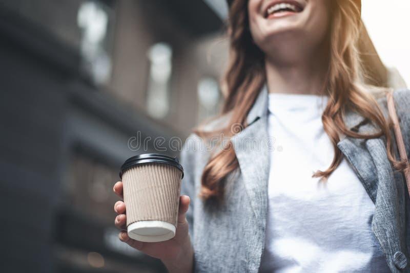 Η νέα εύθυμη γυναίκα κρατά το φλιτζάνι του καφέ στοκ εικόνες