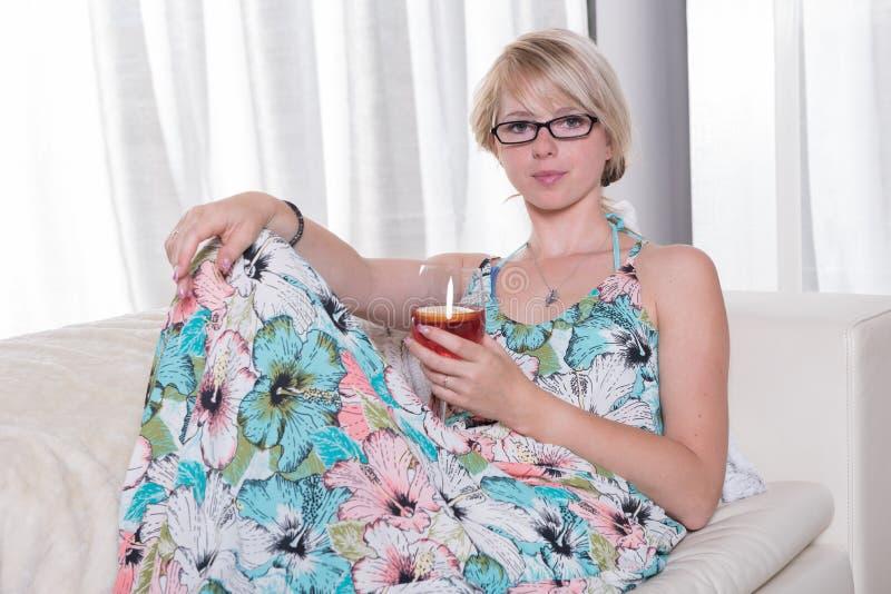 Η νέα ελκυστική γυναίκα απολαμβάνει ένα κοκτέιλ στον καναπέ στοκ εικόνες