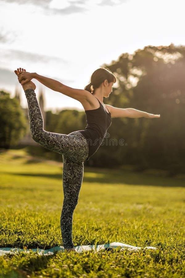 Η νέα ελκυστική γυναίκα που κάνει τη γιόγκα χορευτών θέτει υπαίθρια στον τομέα στοκ φωτογραφίες