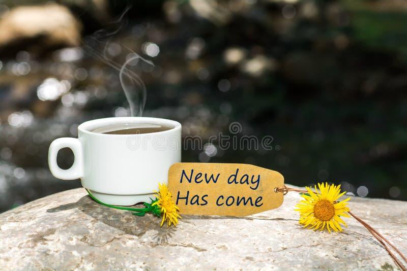 Η νέα ημέρα έχει έρθει κείμενο με το φλυτζάνι καφέ στοκ εικόνες