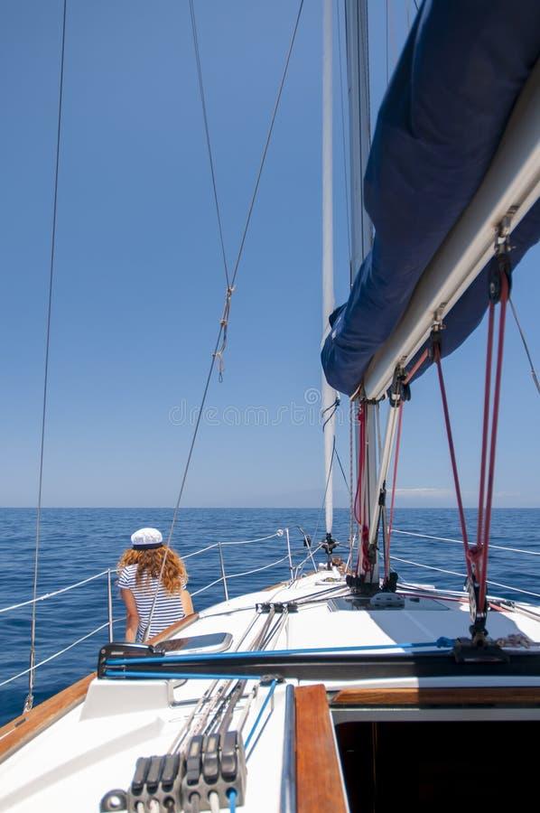 Η νέα θαλάσσια γυναίκα ύφους κάθεται στη βάρκα και κοιτάζει προς τα εμπρός στοκ φωτογραφία με δικαίωμα ελεύθερης χρήσης