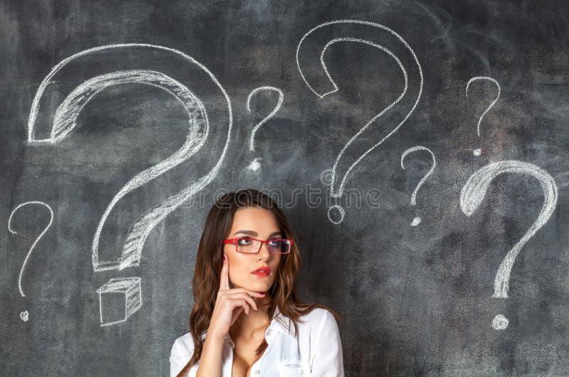 Η νέα θηλυκή επιχειρηματίας στα γυαλιά τα ερωτηματικά στοκ φωτογραφίες