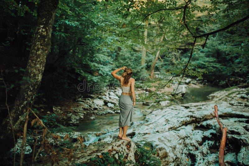 Η νέα και προκλητική γυναίκα κάθεται στο βράχο που φορά το μαγιό στον όμορφο καταρράκτη στη ζούγκλα στοκ φωτογραφίες