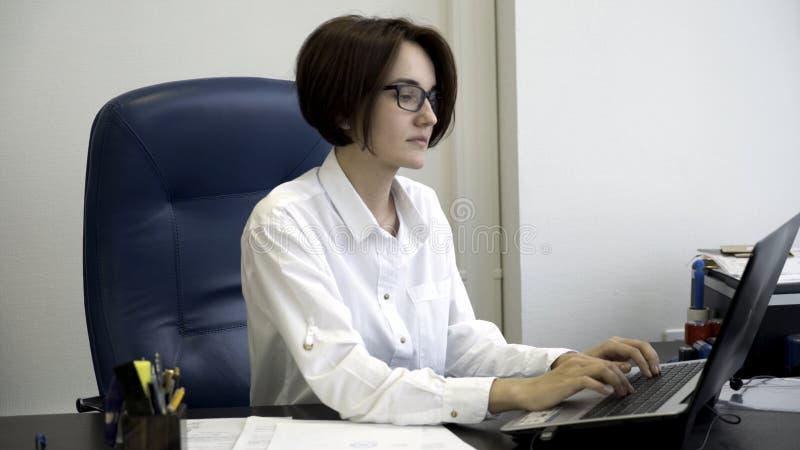 Η νέα και όμορφη επιχειρηματίας με την κοντή, σκοτεινή τρίχα στο άσπρο πουκάμισο είναι κουρασμένη από την εργασία στο γραφείο Νέο στοκ εικόνες