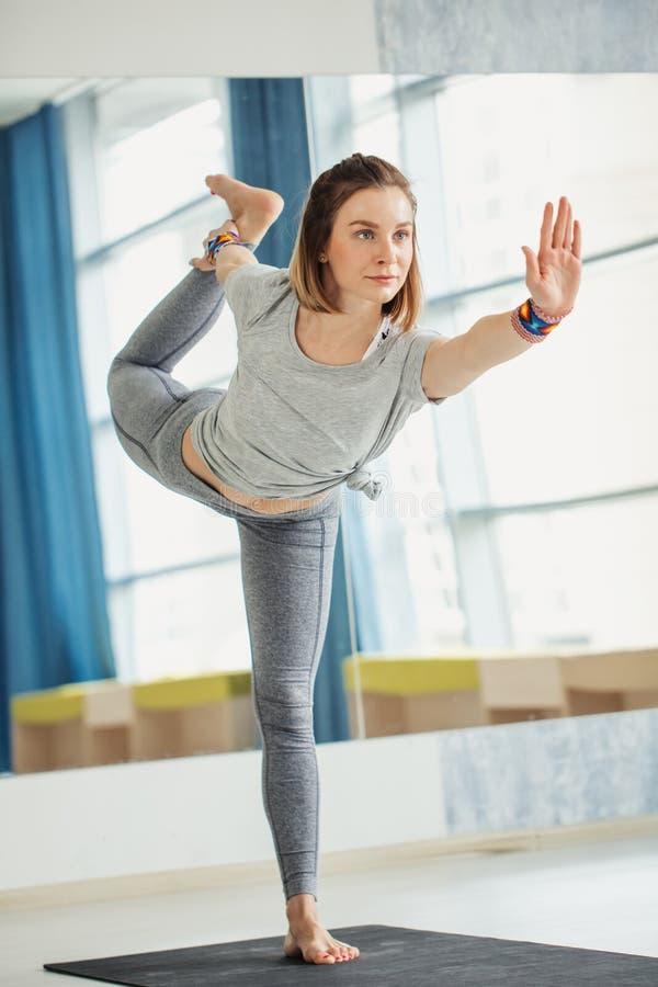 Η νέα κατάλληλη γυναίκα που κάνει μια γιόγκα θέτει τη στάση με ένα πόδι που αυξάνεται επάνω στοκ φωτογραφία