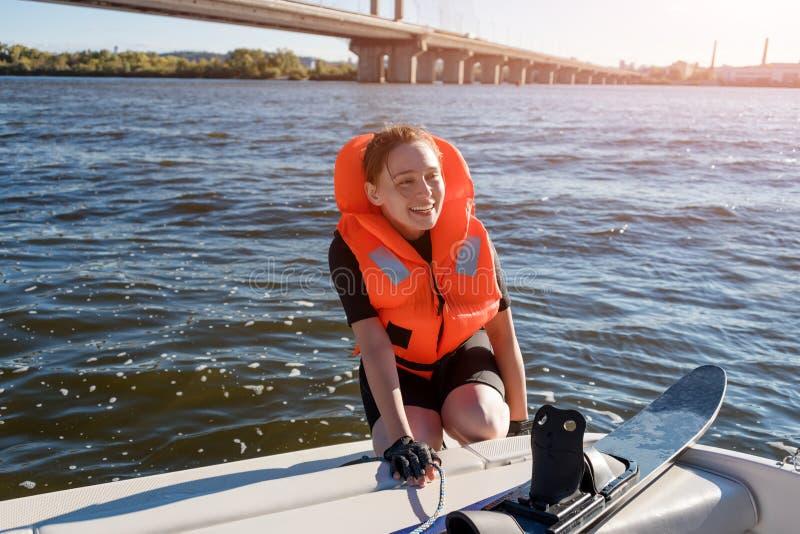 Η νέα κατάλληλη γυναίκα έτοιμη να οδηγήσει το νερό κάνει σκι εγκαθιστώντας στην κινηματογράφηση σε πρώτο πλάνο βαρκών Νερό αθλητώ στοκ φωτογραφίες
