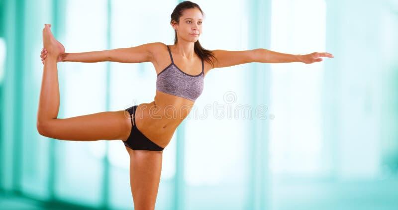 Η νέα καυκάσια γυναίκα κάνει τη γιόγκα στη γυμναστική στοκ φωτογραφία