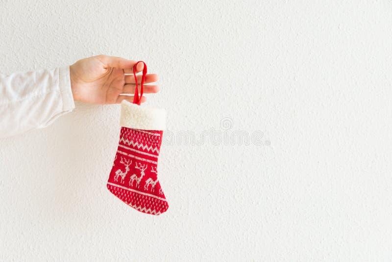 Η νέα καυκάσια γυναίκα κρατά τη υπό εξέταση πλεκτή κόκκινη γυναικεία κάλτσα δώρων Χριστουγέννων στο άσπρο υπόβαθρο τοίχων Η οικογ στοκ εικόνα