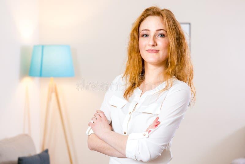 Η νέα καυκάσια στάση κοριτσιών στο γραφείο και διπλωμένος τα όπλα της πέρα από το θωρακικό γοητευτικό νέο κορίτσι της λειτουργεί  στοκ εικόνες