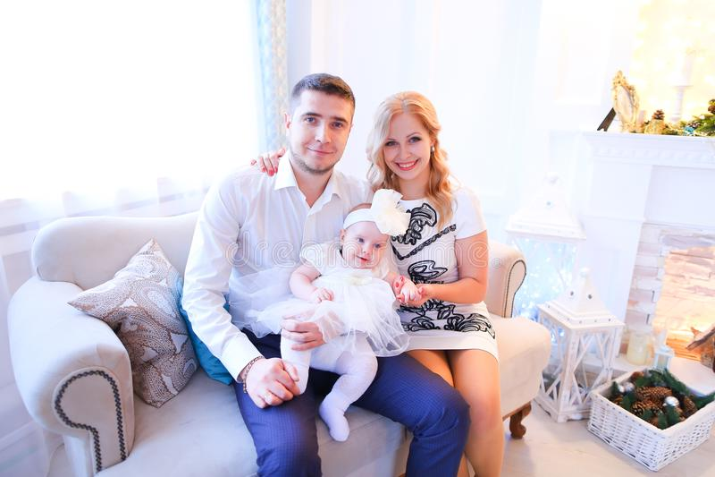 Η νέα καυκάσια συνεδρίαση πατέρων και μητέρων με την κόρη στον καναπέ διακόσμησε πλησίον την εστία στοκ εικόνα με δικαίωμα ελεύθερης χρήσης