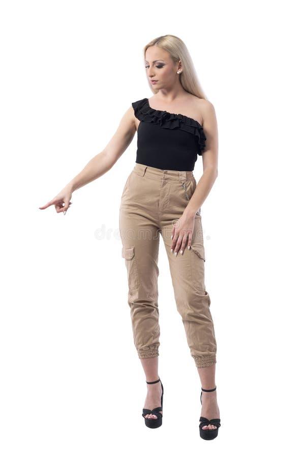 Η νέα κομψή ξανθή γυναίκα στην πολυτέλεια ντύνει την υπόδειξη του δάχτυλου και την επιλογή ψωνίζοντας στοκ εικόνα