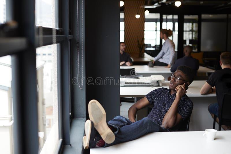 Η νέα μαύρη αρσενική δημιουργική συνεδρίαση σε ένα γραφείο με τα πόδια του επάνω στο γραφείο που χρησιμοποιεί το τηλέφωνο, κλείνε στοκ φωτογραφίες με δικαίωμα ελεύθερης χρήσης