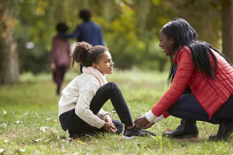 Η νέα μαύρη γυναίκα που βοηθά την κόρη της για να δέσει τα παπούτσια της κατά τη διάρκεια μιας οικογένειας περπατά στο πάρκο, χαμ στοκ εικόνα με δικαίωμα ελεύθερης χρήσης