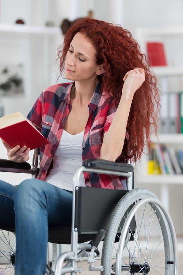 Η νέα με ειδικές ανάγκες γυναίκα Disabilty και αναπηρίας στην αναπηρική καρέκλα διαβάζει το βιβλίο στοκ εικόνες