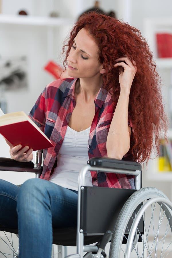 Η νέα με ειδικές ανάγκες γυναίκα Disabilty και αναπηρίας στην αναπηρική καρέκλα διαβάζει το βιβλίο στοκ εικόνα