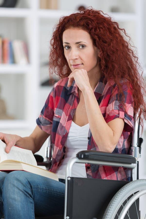 Η νέα με ειδικές ανάγκες γυναίκα Disabilty και αναπηρίας στην αναπηρική καρέκλα διαβάζει το βιβλίο στοκ εικόνες με δικαίωμα ελεύθερης χρήσης