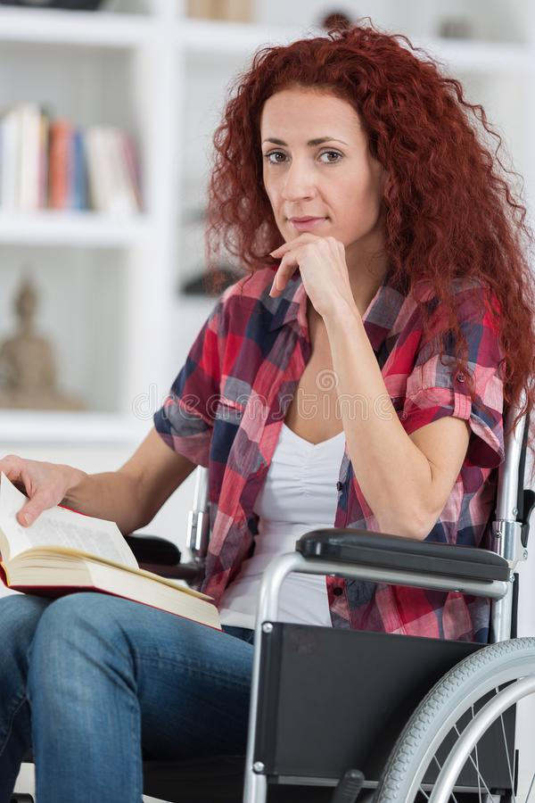Η νέα με ειδικές ανάγκες γυναίκα Disabilty και αναπηρίας στην αναπηρική καρέκλα διαβάζει το βιβλίο στοκ εικόνα με δικαίωμα ελεύθερης χρήσης