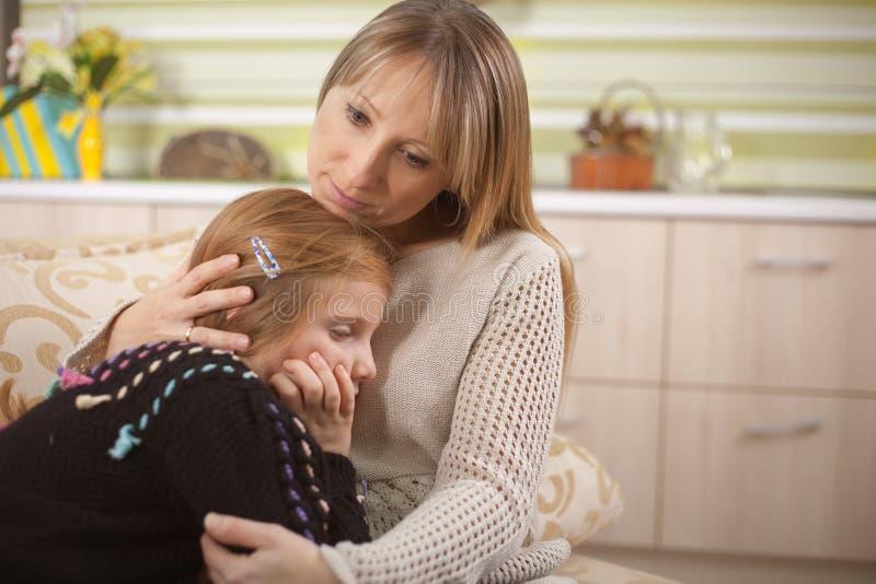 Η νέα μητέρα ανακουφίζει τη λυπημένη κόρη της στοκ εικόνες