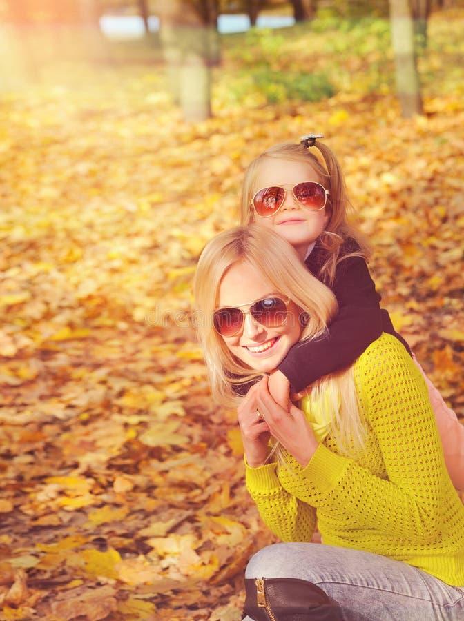 Η νέα μητέρα και λίγη παίζοντας μόδα κορών έντυσαν στα γυαλιά ηλίου στο πάρκο φθινοπώρου στοκ εικόνα