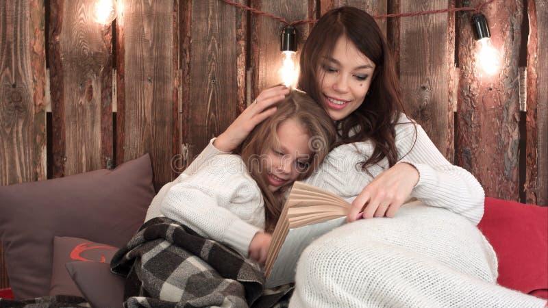 Η νέα μητέρα με ένα βιβλίο που βρίσκεται σε έναν καναπέ και που αγκαλιάζει την λίγη κόρη στα Χριστούγεννα διακόσμησε το εσωτερικό στοκ εικόνα