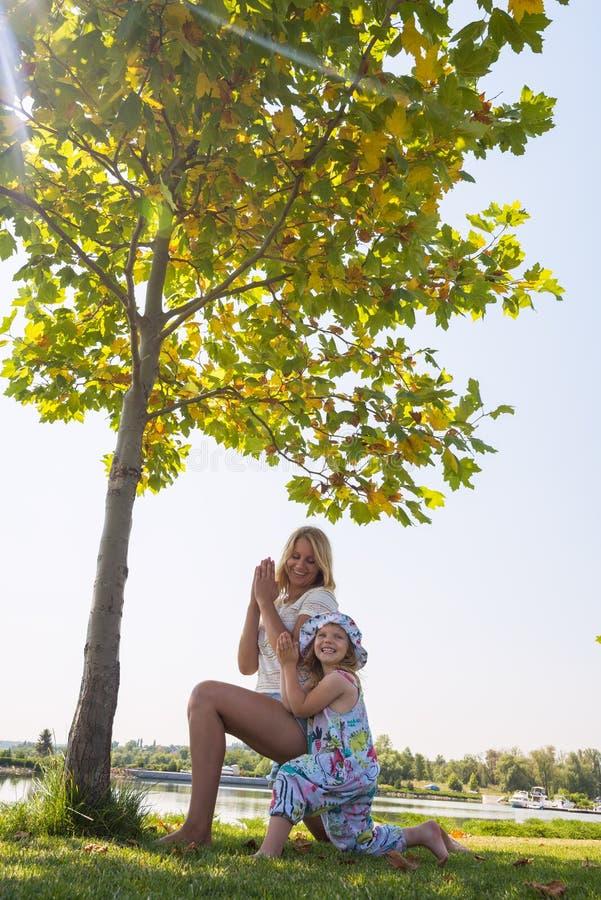 Η νέα μητέρα με την λίγη γελώντας κόρη συμμετέχει στο yog στοκ εικόνα με δικαίωμα ελεύθερης χρήσης