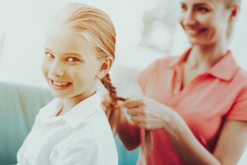 Η νέα μητέρα πλέκει μια πλεξίδα κορών ` s στοκ εικόνες