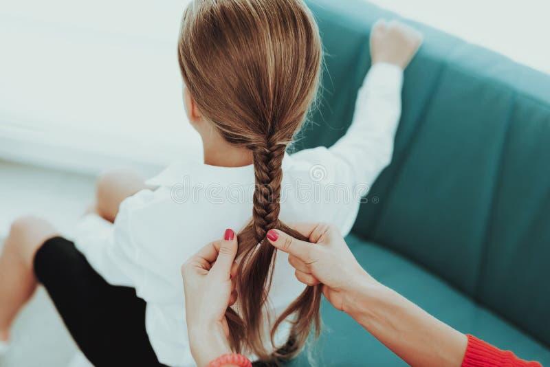 Η νέα μητέρα πλέκει μια πλεξίδα κορών ` s στοκ φωτογραφία