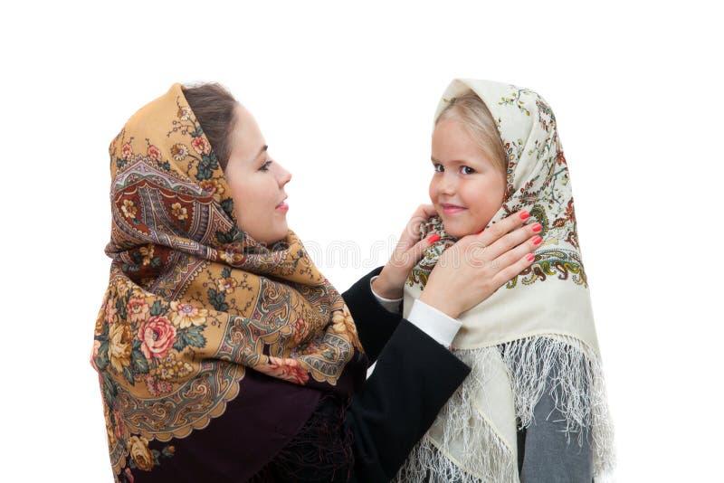 Η νέα μητέρα ρυθμίζει το σάλι της στην επικεφαλής κόρη στοκ εικόνες