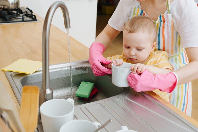 Η νέα μητέρα σε μια κουζίνα πλένει τα φλυτζάνια και τα πιάτα Λίγος γιος βοηθά στοκ φωτογραφίες