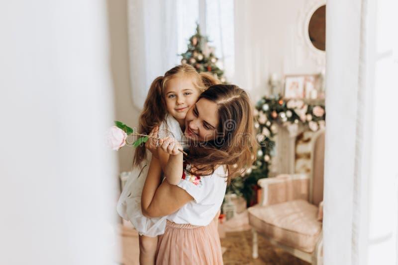 Η νέα μητέρα την κρατά σε ετοιμότητα της λίγη κόρη στο άνετο δωμάτιο με στοκ φωτογραφίες