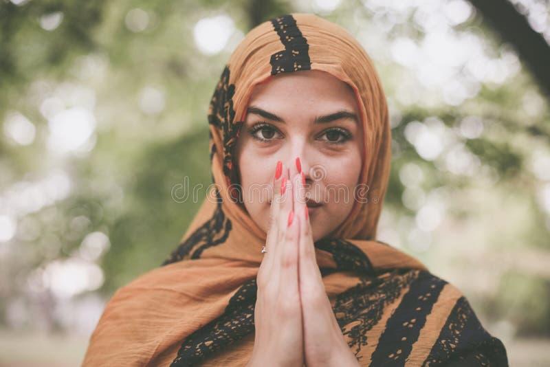 Η νέα μουσουλμανική γυναίκα παίρνει την επίκληση θέτει στοκ εικόνα με δικαίωμα ελεύθερης χρήσης