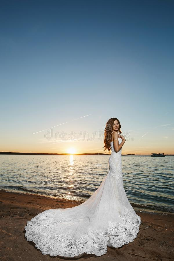 Η νέα νύφη brunette, όμορφο πρότυπο κορίτσι, στο άσπρο φόρεμα δαντελλών, στέκεται στην ακτή στο ηλιοβασίλεμα στοκ φωτογραφία με δικαίωμα ελεύθερης χρήσης