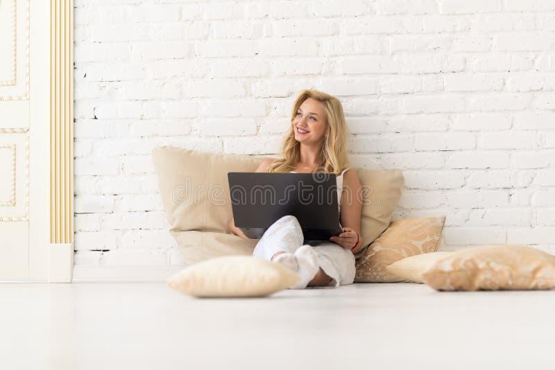 Η νέα ξανθή γυναίκα κάθεται στο πάτωμα στα μαξιλάρια χρησιμοποιώντας το φορητό προσωπικό υπολογιστή, όμορφο ευτυχές χαμόγελο κορι στοκ φωτογραφία με δικαίωμα ελεύθερης χρήσης