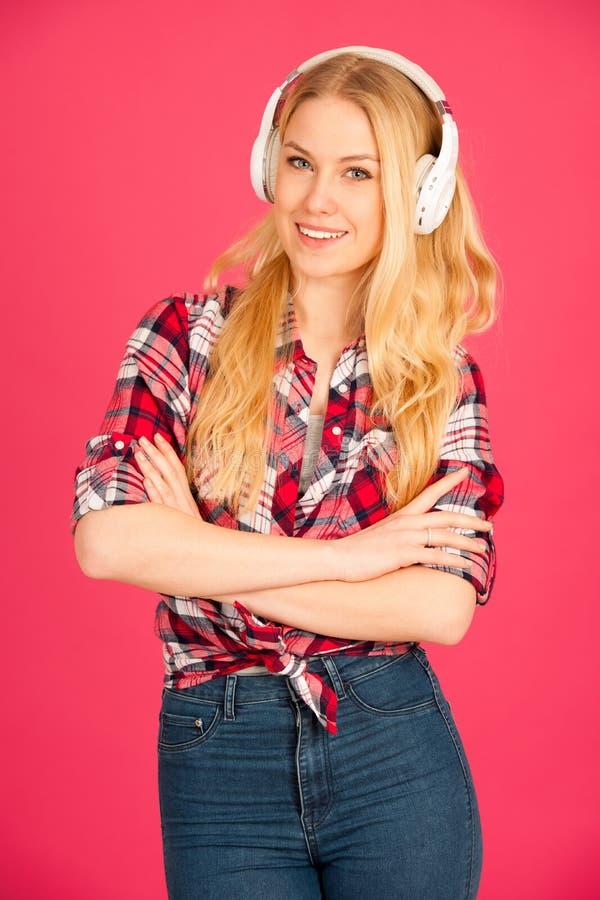 Η νέα ξανθή γυναίκα με τα ακουστικά ακούει τη μουσική άνω του pi στοκ φωτογραφίες με δικαίωμα ελεύθερης χρήσης