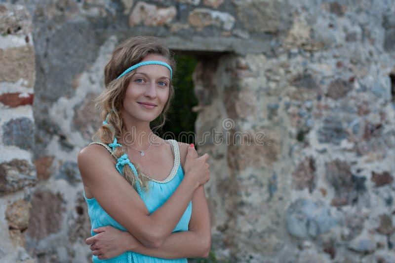 Η νέα ξανθή γυναίκα με τα μπλε μάτια και πλεγμένος ακούει τη φθορά turq στοκ φωτογραφία με δικαίωμα ελεύθερης χρήσης