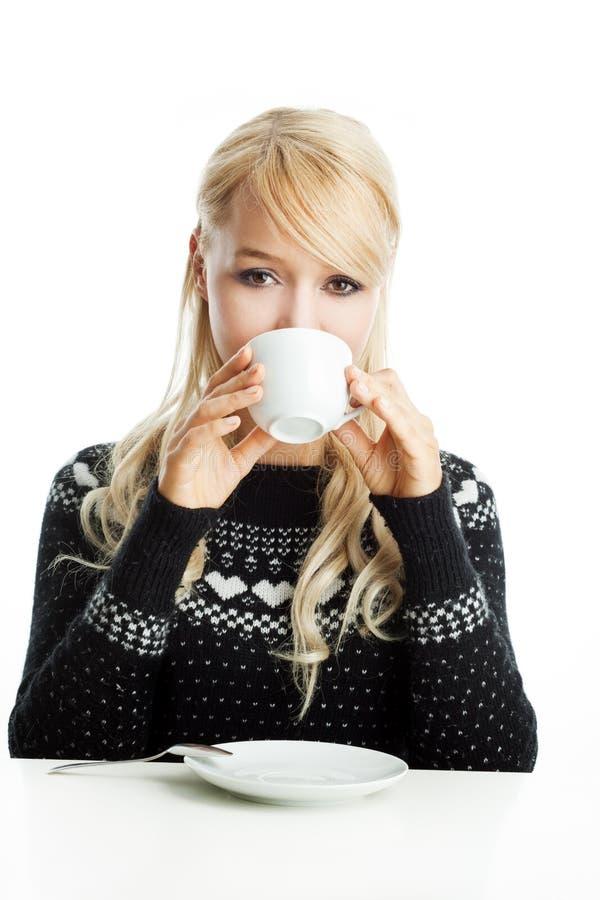 Η νέα ξανθή γυναίκα πίνει ένα φλιτζάνι του καφέ ή ένα τσάι στοκ εικόνες