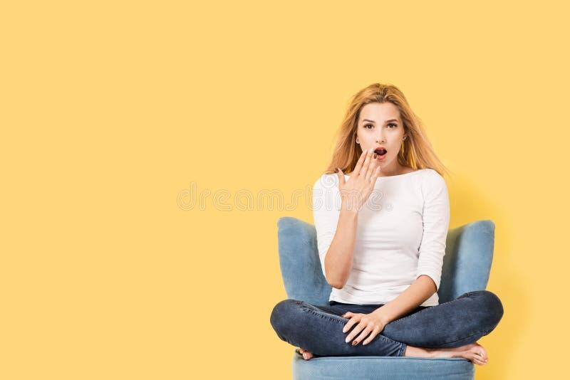 Η νέα ξανθή γυναίκα στην καρέκλα είναι έκπληκτη στοκ φωτογραφία με δικαίωμα ελεύθερης χρήσης