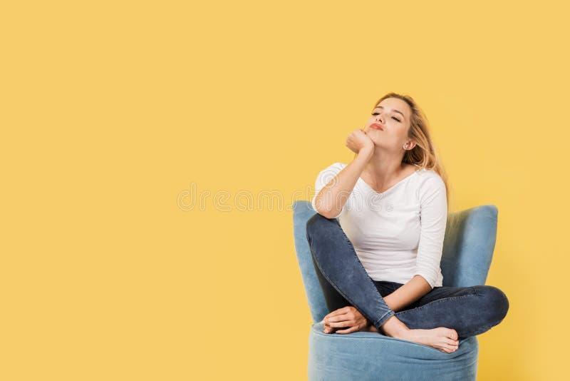 Η νέα ξανθή γυναίκα στην καρέκλα είναι βαριεστημένη στοκ φωτογραφία με δικαίωμα ελεύθερης χρήσης