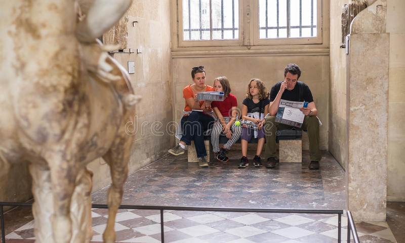 Η νέα οικογένεια στηρίζεται σε έναν πάγκο στη στοά του αρχαίου γλυπτού, Λ στοκ φωτογραφία με δικαίωμα ελεύθερης χρήσης