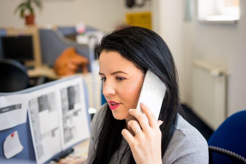 Η νέα ομιλία γυναικών στο κινητό τηλέφωνο στην εργασία και συμβουλεύει τους πελάτες στοκ φωτογραφία