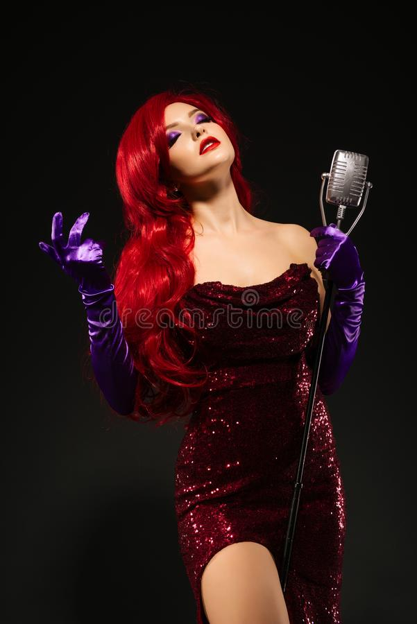 Η νέα ρομαντική redhead γυναίκα με πολύ μακρυμάλλη στο κόκκινο φόρεμα με το μικρόφωνο στη στάση τραγουδά με τις προσοχές του ιδια στοκ εικόνες