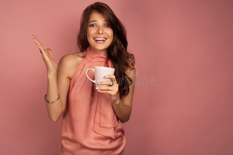 Η νέα σκοτεινός-μαλλιαρή γυναίκα με το ρόδινο φλυτζάνι στο χέρι της χαμογελά εκπληκτικά στη κάμερα, ρόδινο υπόβαθρο στοκ φωτογραφία με δικαίωμα ελεύθερης χρήσης