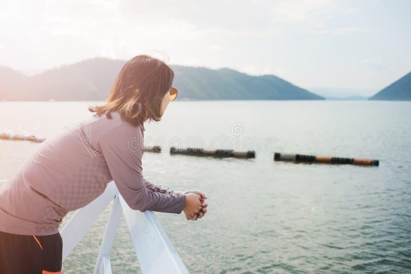 Η νέα στάση γυναικών μόνο στο μέτωπο μπαλκονιών της έχει τη θάλασσα, mountai στοκ εικόνες με δικαίωμα ελεύθερης χρήσης
