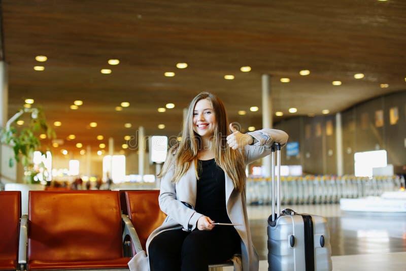 Η νέα συμπαθητική συνεδρίαση γυναικών στην αίθουσα αερολιμένων με την ταμπλέτα και, παρουσιάζοντας αντίχειρες στοκ εικόνες